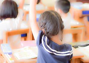 教室で手を挙げる子供たち