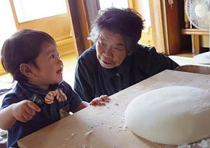 おばあちゃんの隣に座る幼児